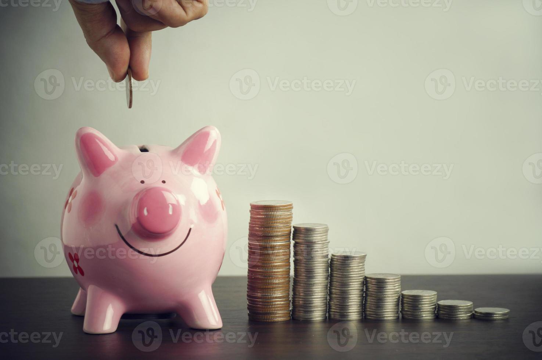 Hand putting money in a piggy jar photo