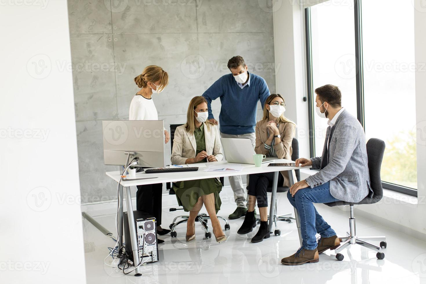 Masked professionals in a meeting in a modern office photo
