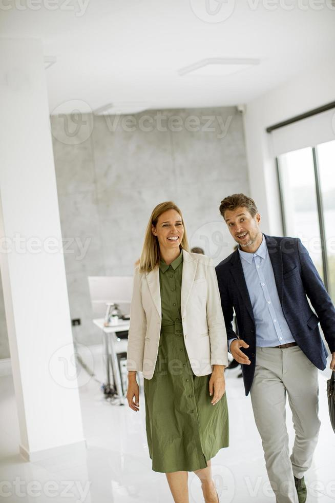 Business professionals walking together in office space photo