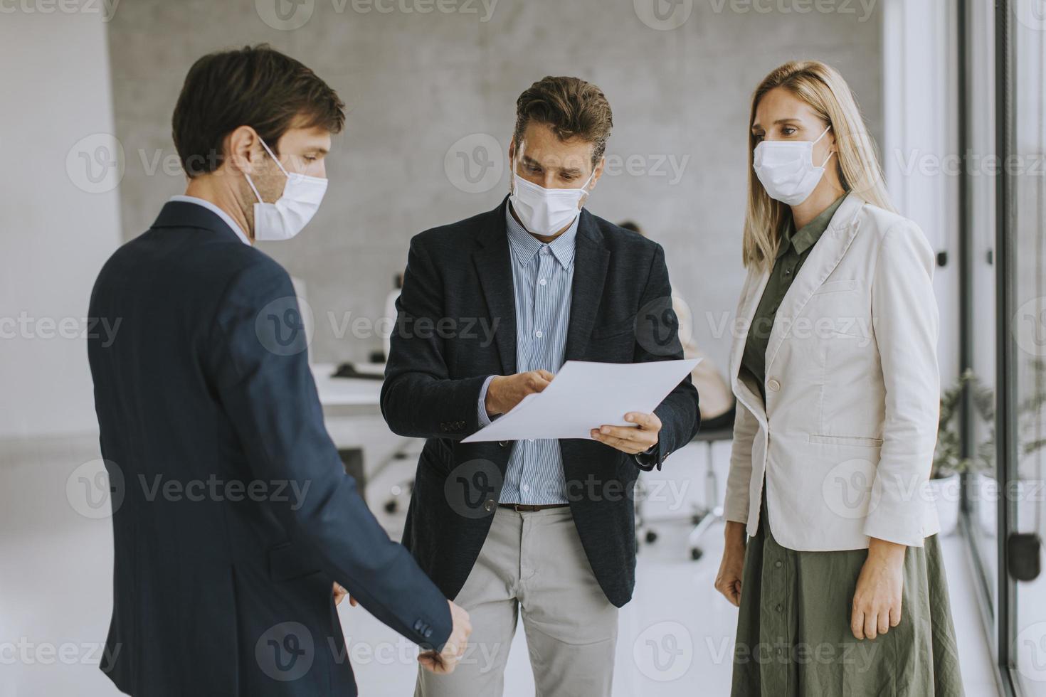 Tres profesionales discutiendo documentos con máscaras foto