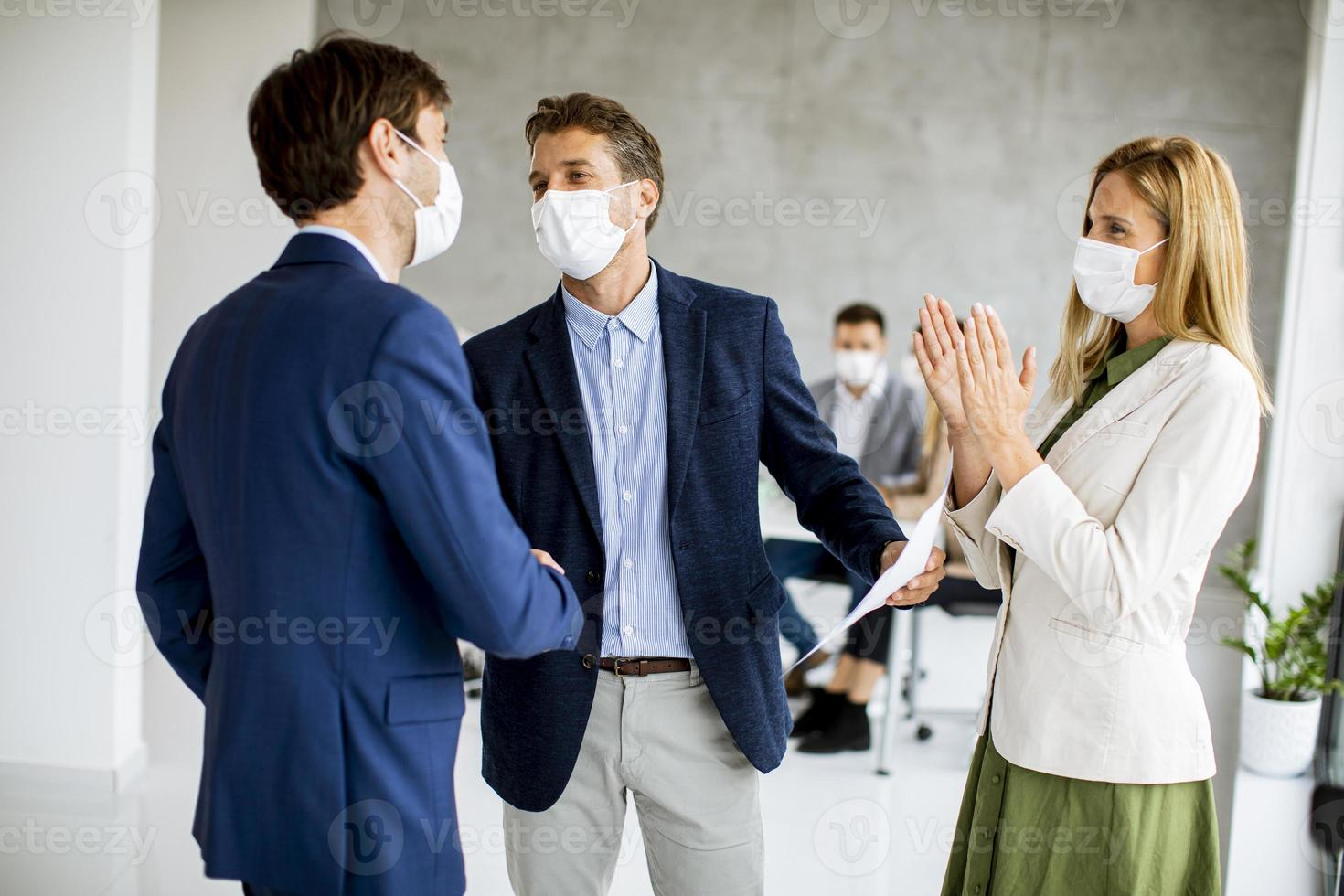 Three masked business people making agreement photo