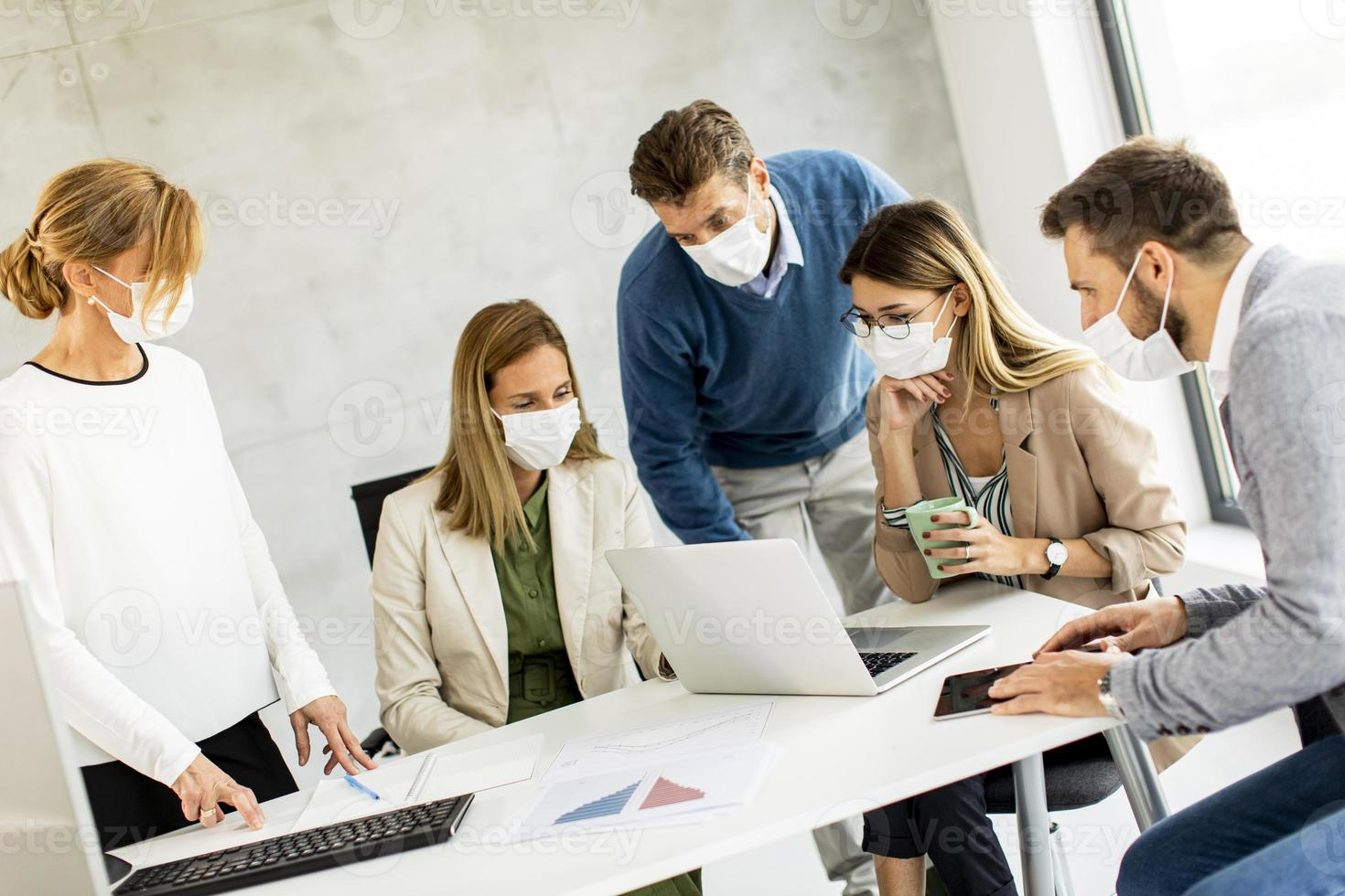 equipo enmascarado mirando una computadora portátil foto