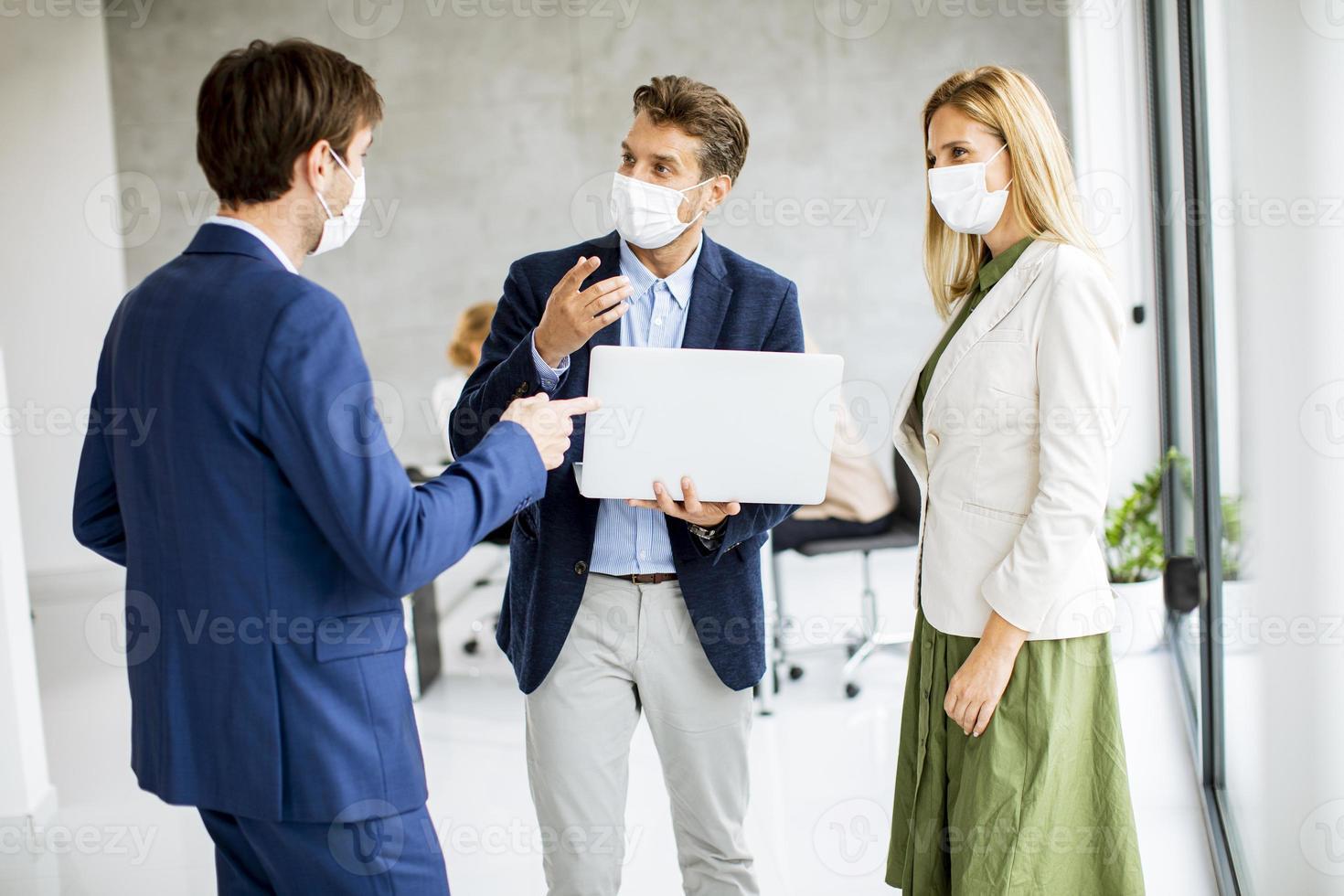 Tres profesionales enmascarados de pie y hablando. foto