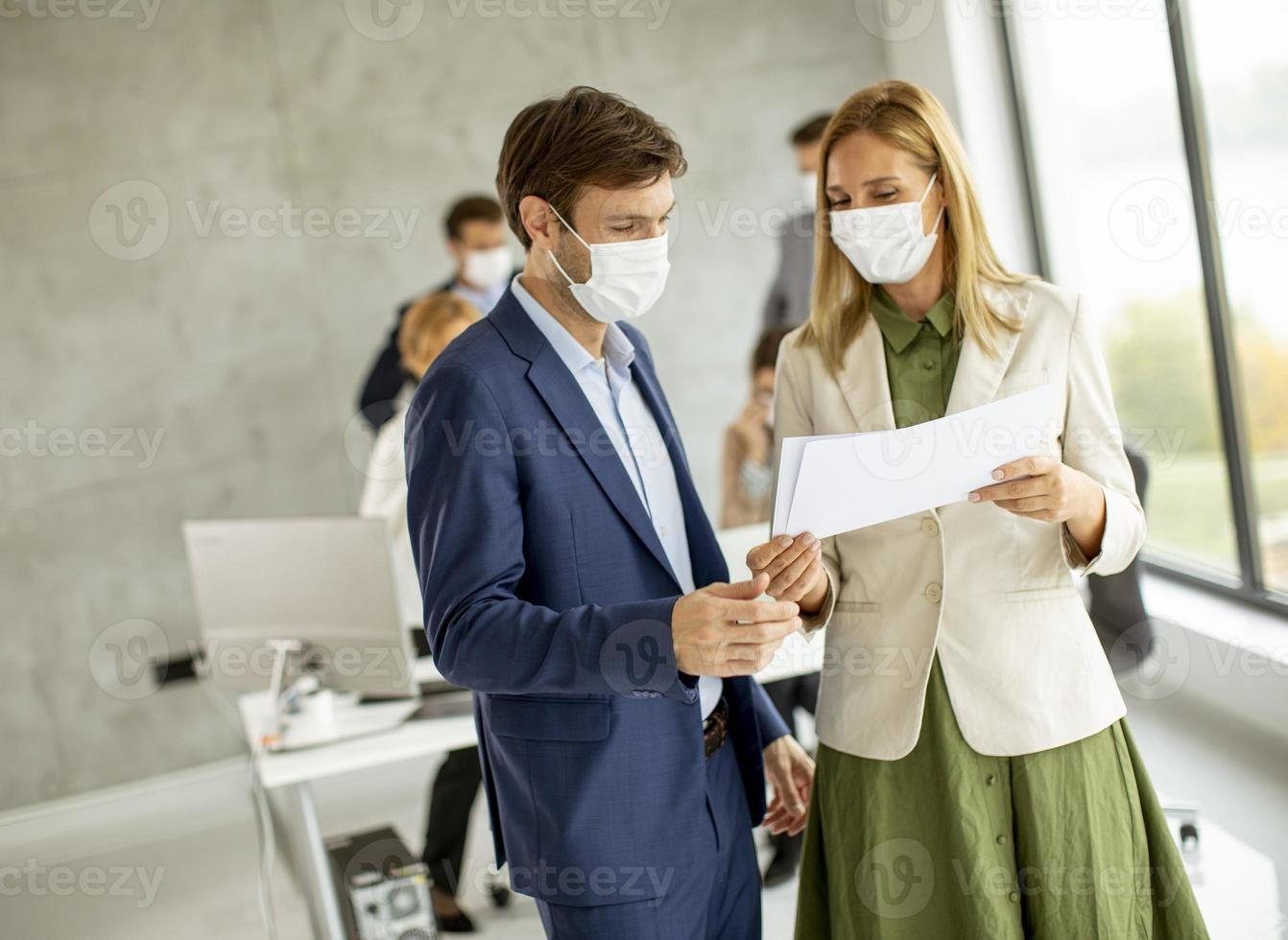Two masked professionals looking at a document photo