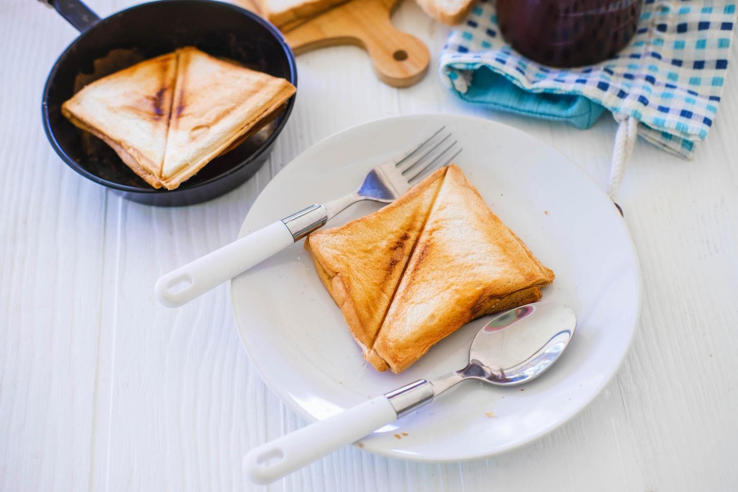 pan tostado tostado saliendo de una tostadora de acero inoxidable en la cocina de una casa. foto