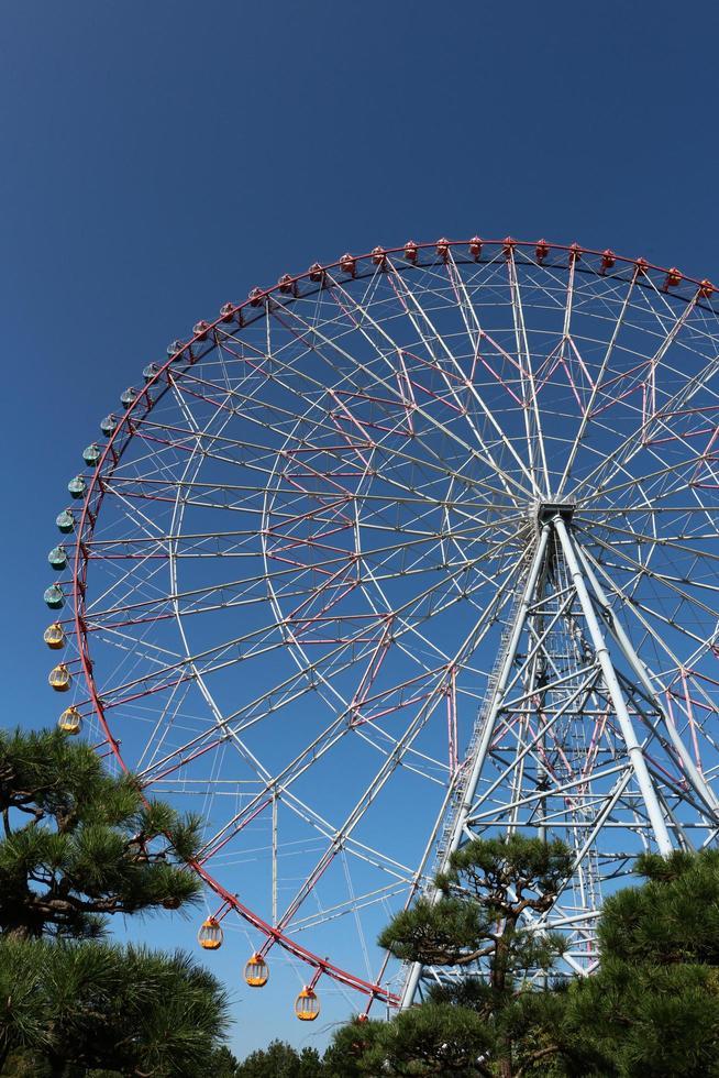 noria con cielo azul en el parque de atracciones foto