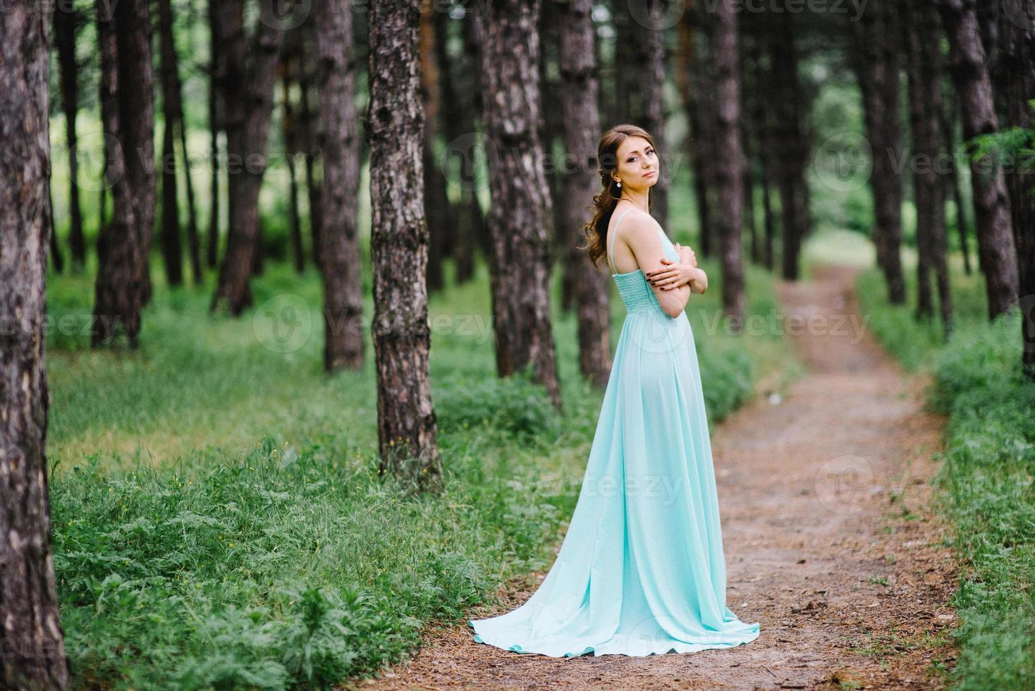 niña feliz en un vestido largo turquesa en un parque verde foto
