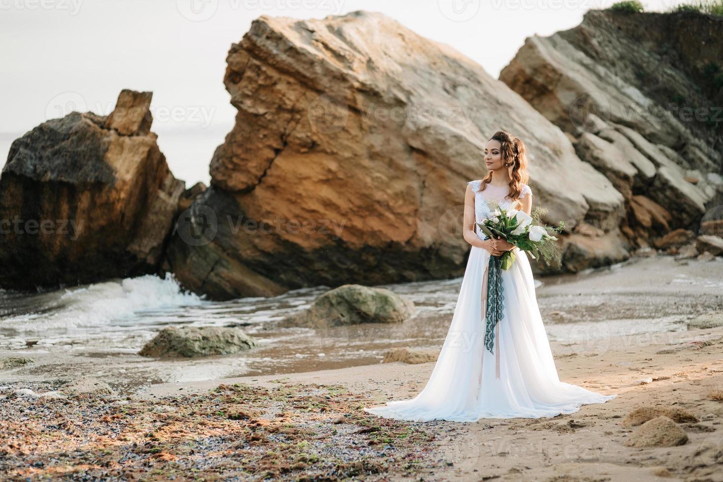 novia con un ramo de novia en la orilla foto