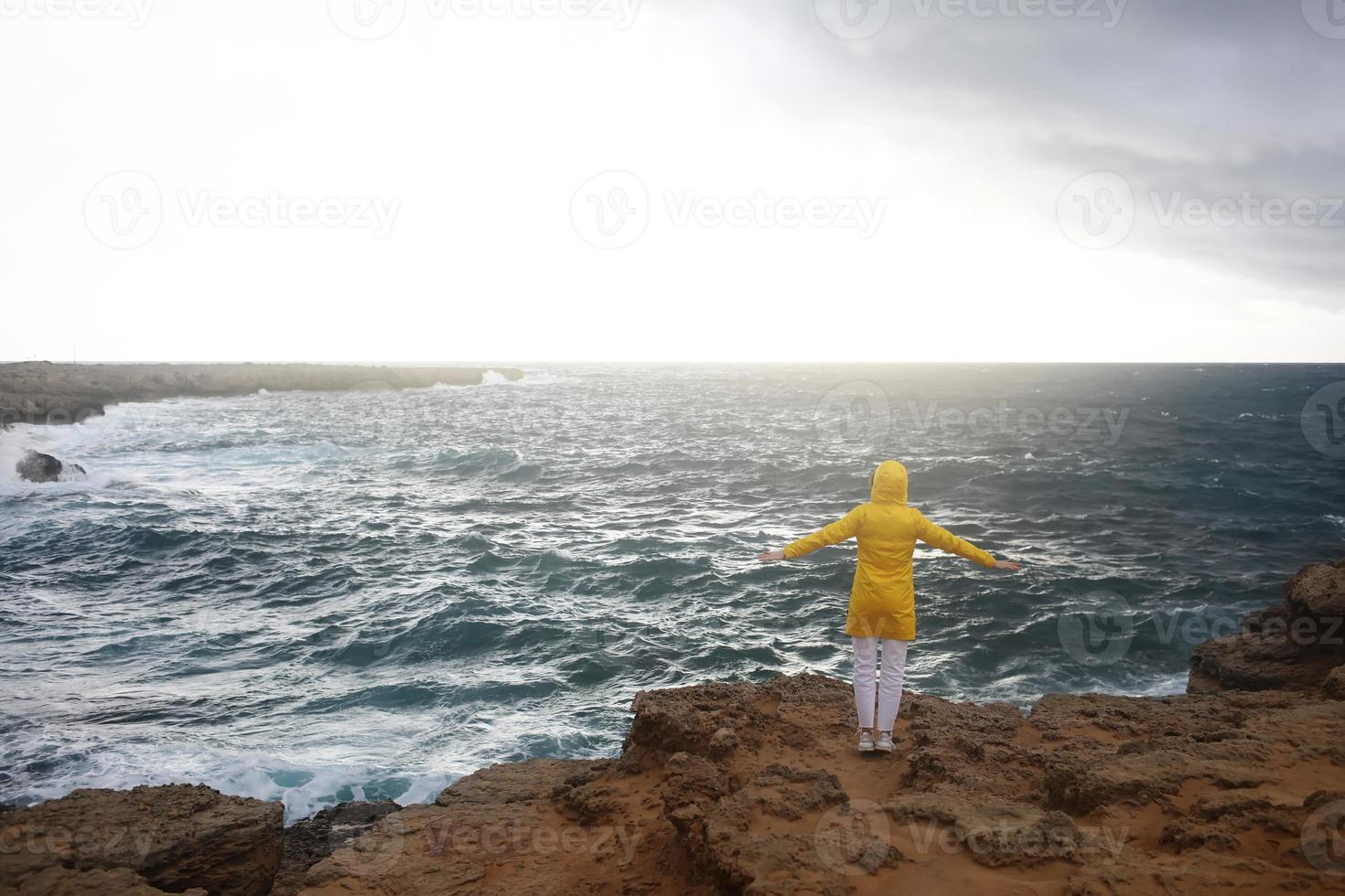 Young woman dressed in yellow raincoat standing with outstretched arms while enjoying beautiful sea landscape photo