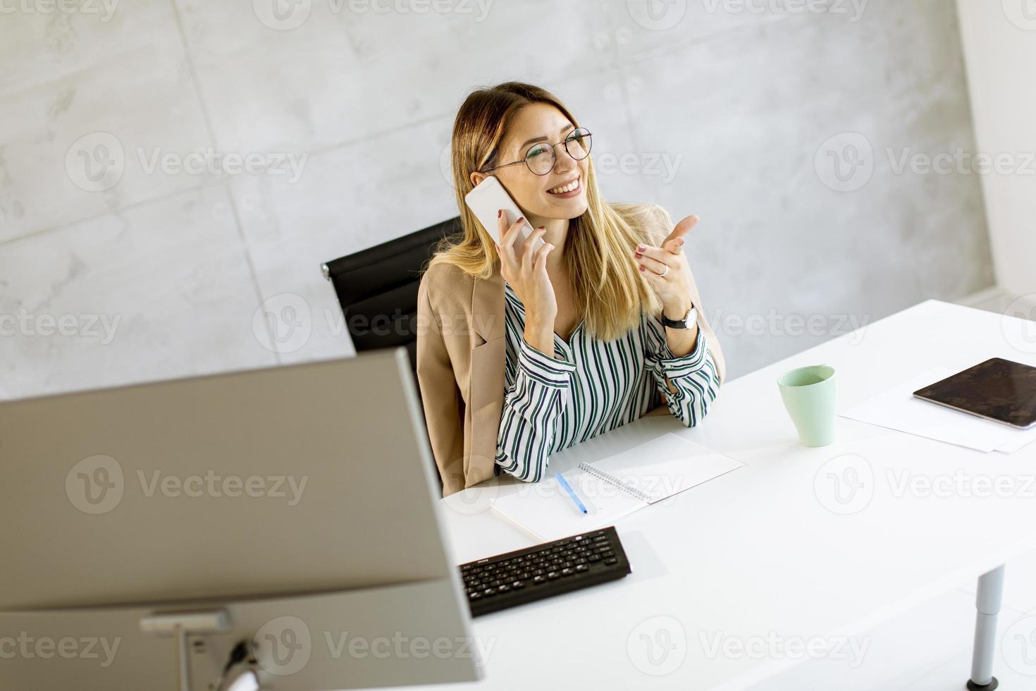 mujer de negocios, en, teléfono, en el escritorio foto