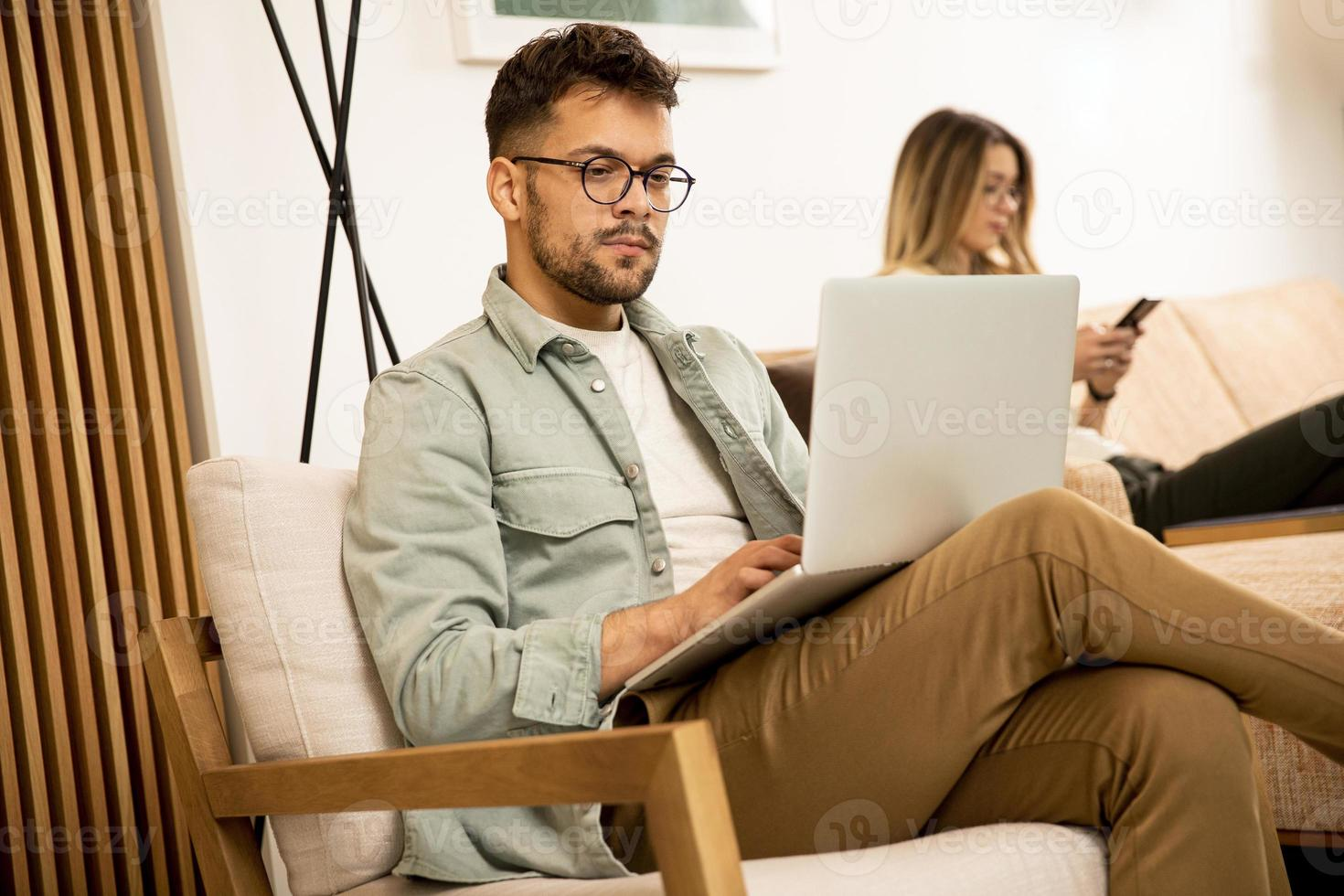 Young man using laptop at home photo