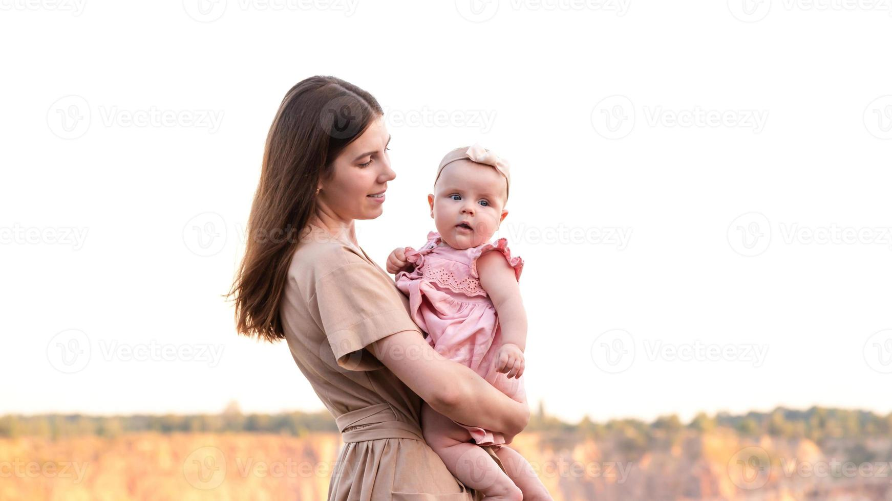 Feliz joven madre sostiene a su pequeña hija en sus brazos foto