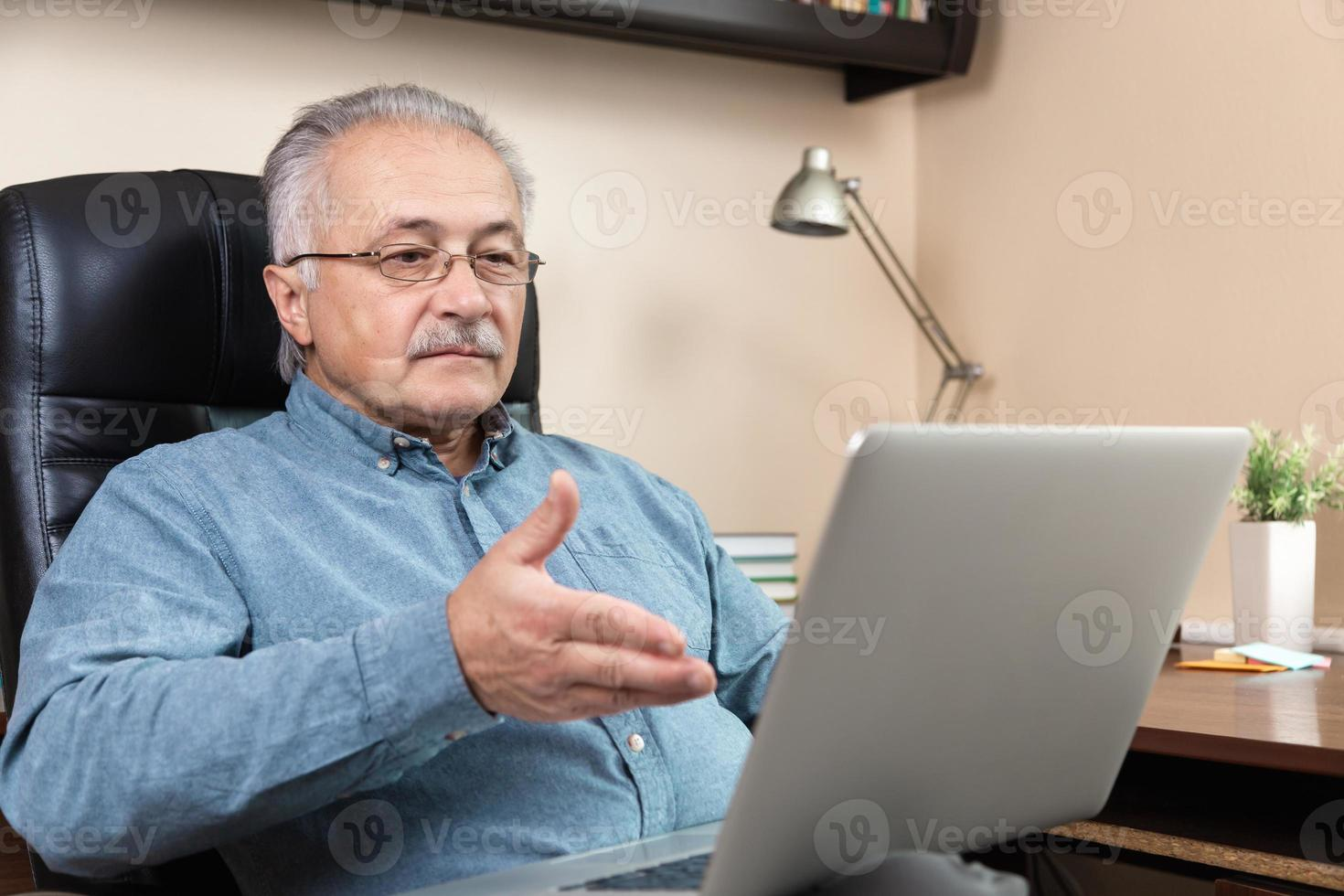 Old man makes video call talking with relatives or friends by video conference app photo
