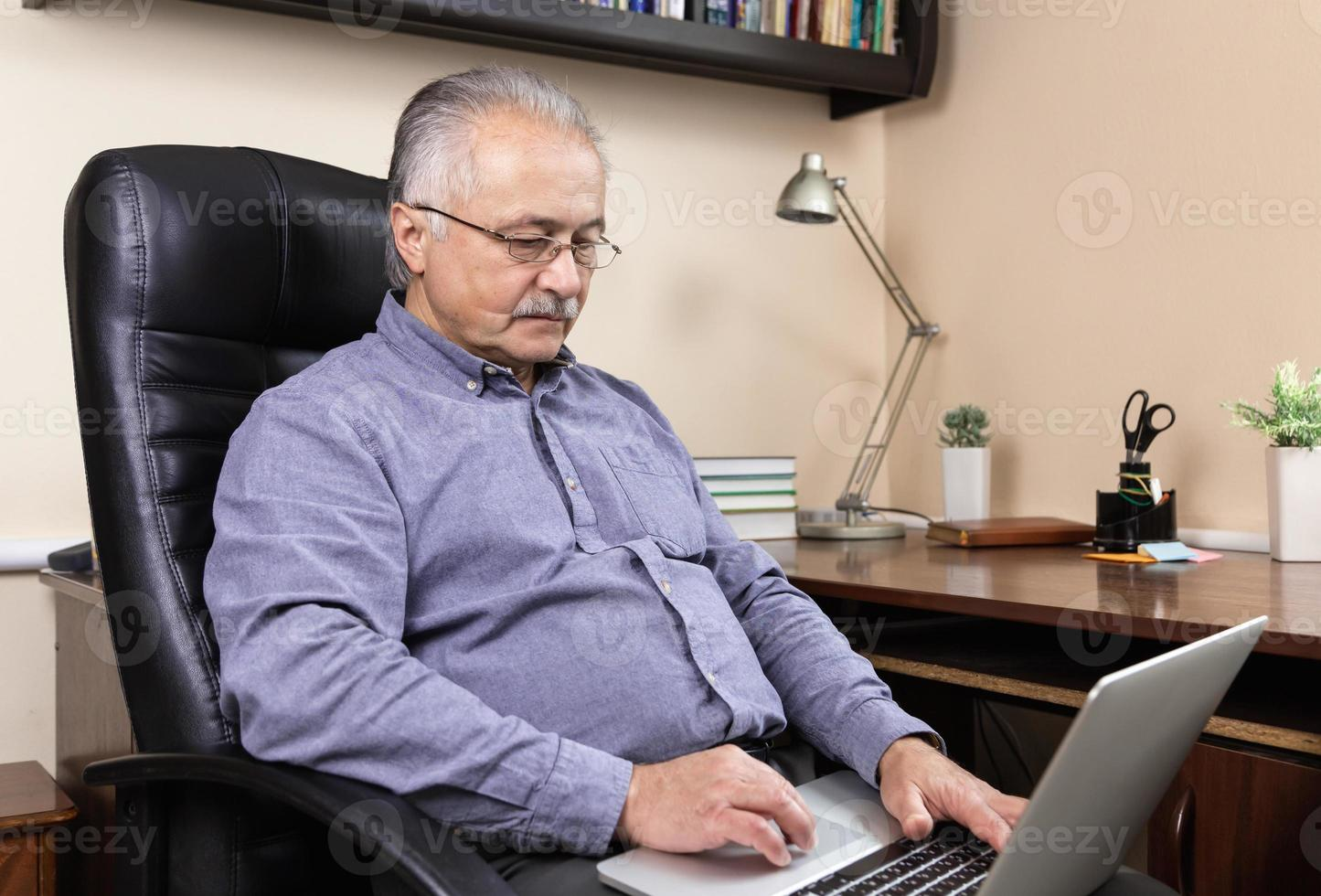 Senior man learns to use the computer photo