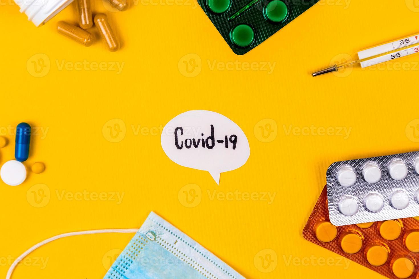 Mascarilla de protección médica de algodón azul sobre un fondo de papel amarillo con pastillas foto