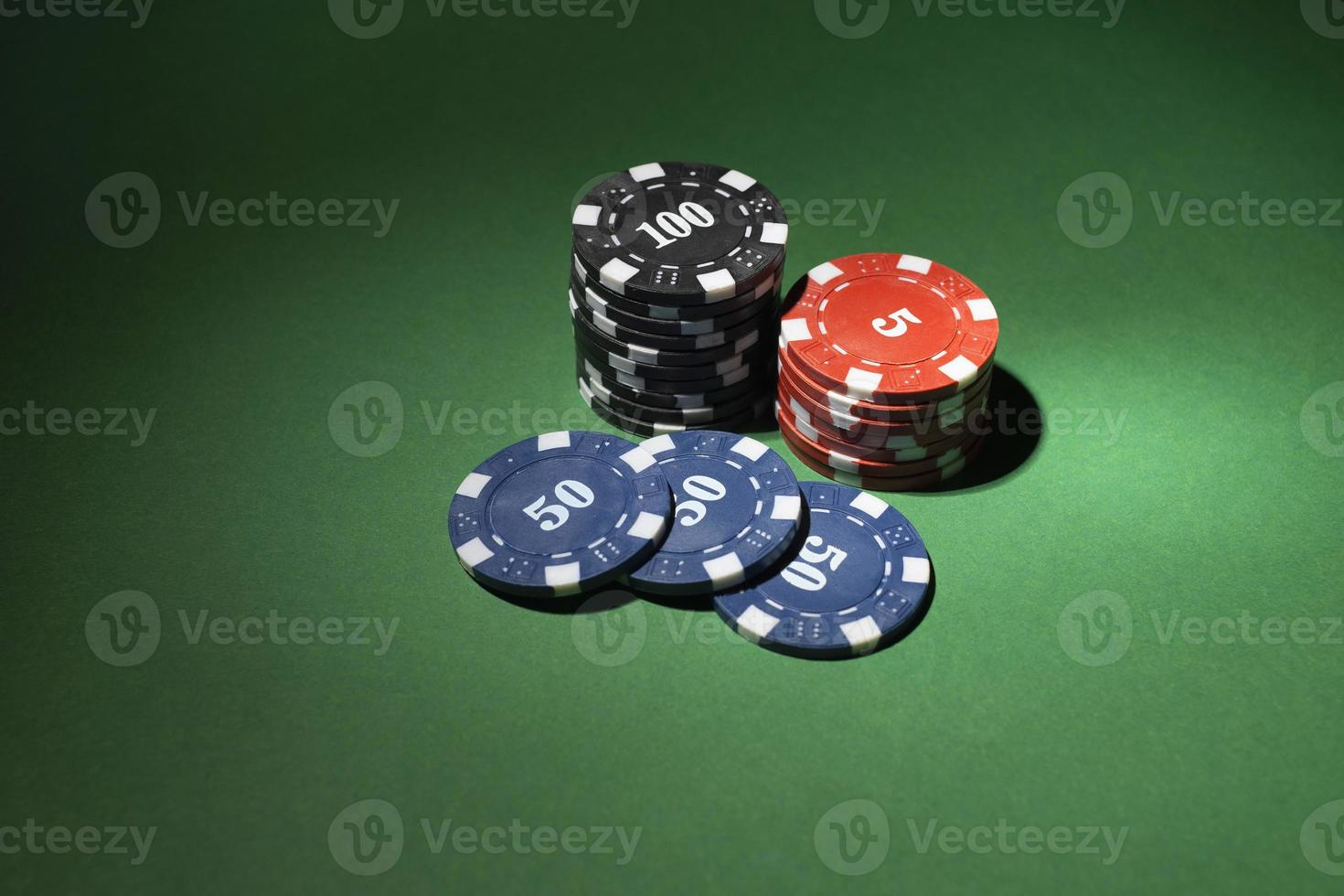Stacked casino tokens on green background photo