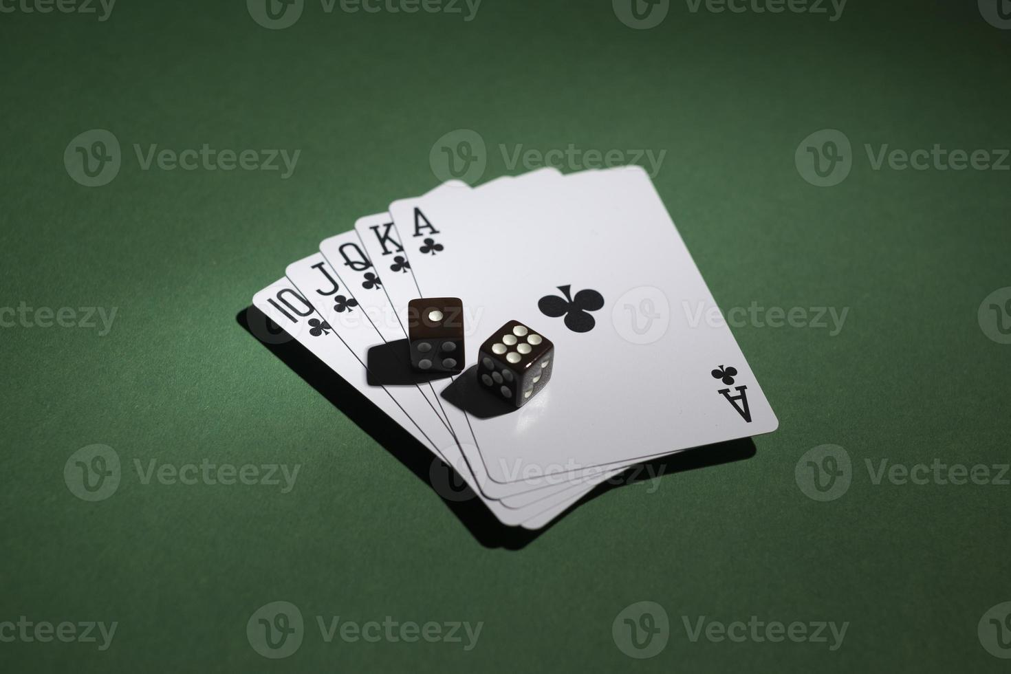 Royal flush cards with dices on green background photo