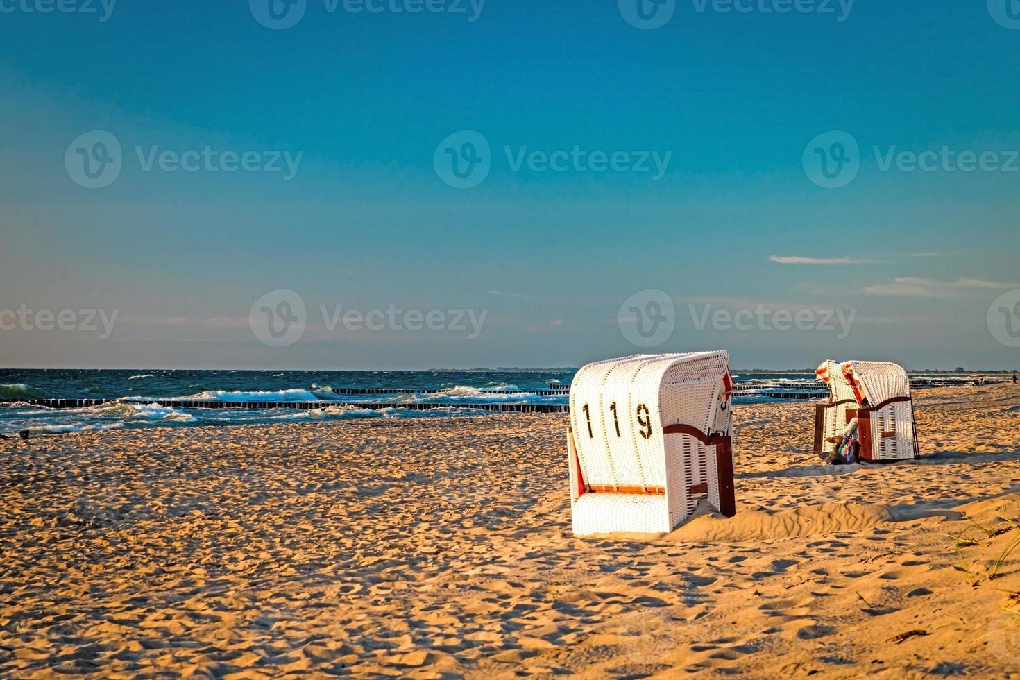Sillas de playa de pie en la puesta de sol en una playa en el mar Báltico con mar foto