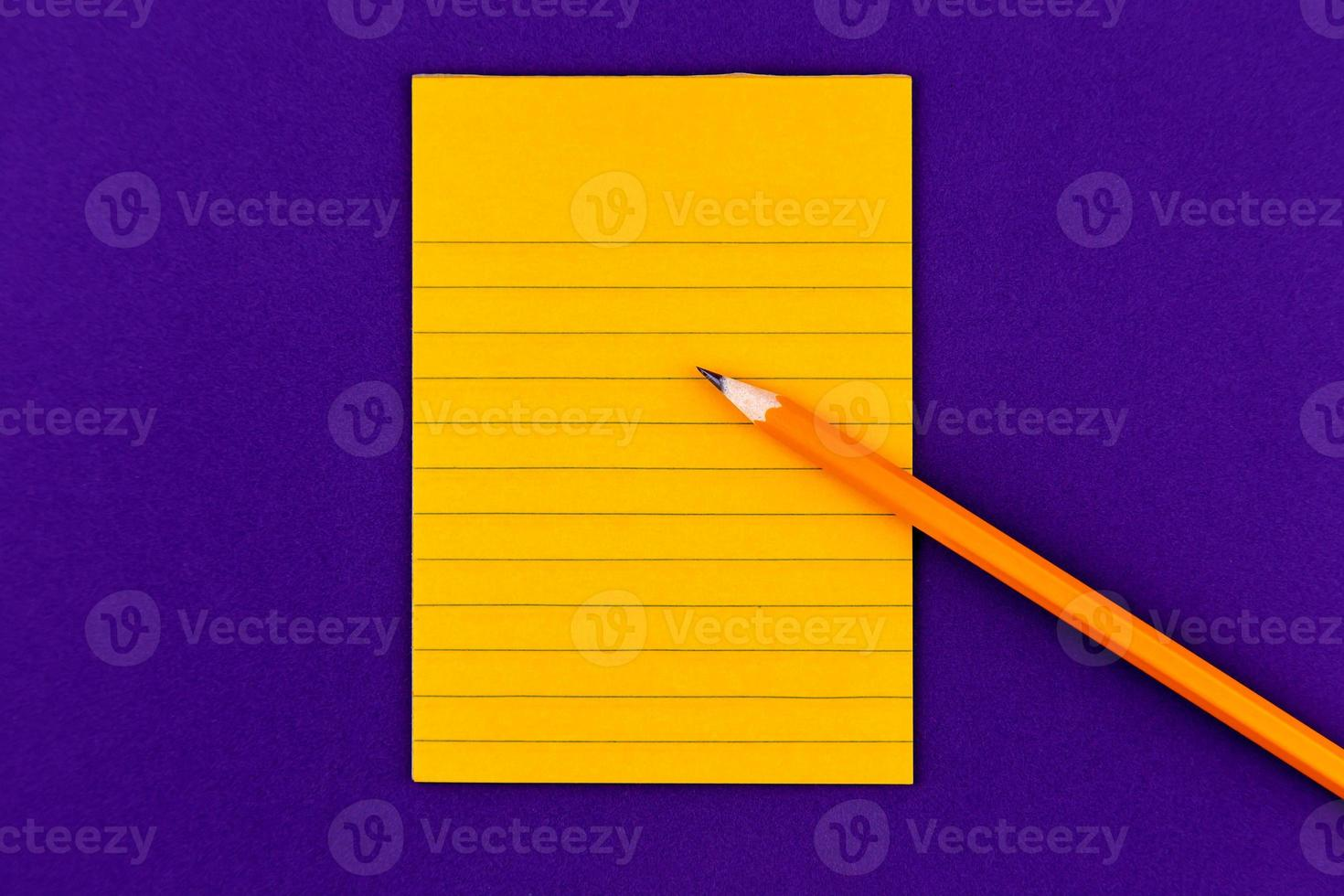 Orange sheet of paper and pencil on purple background photo