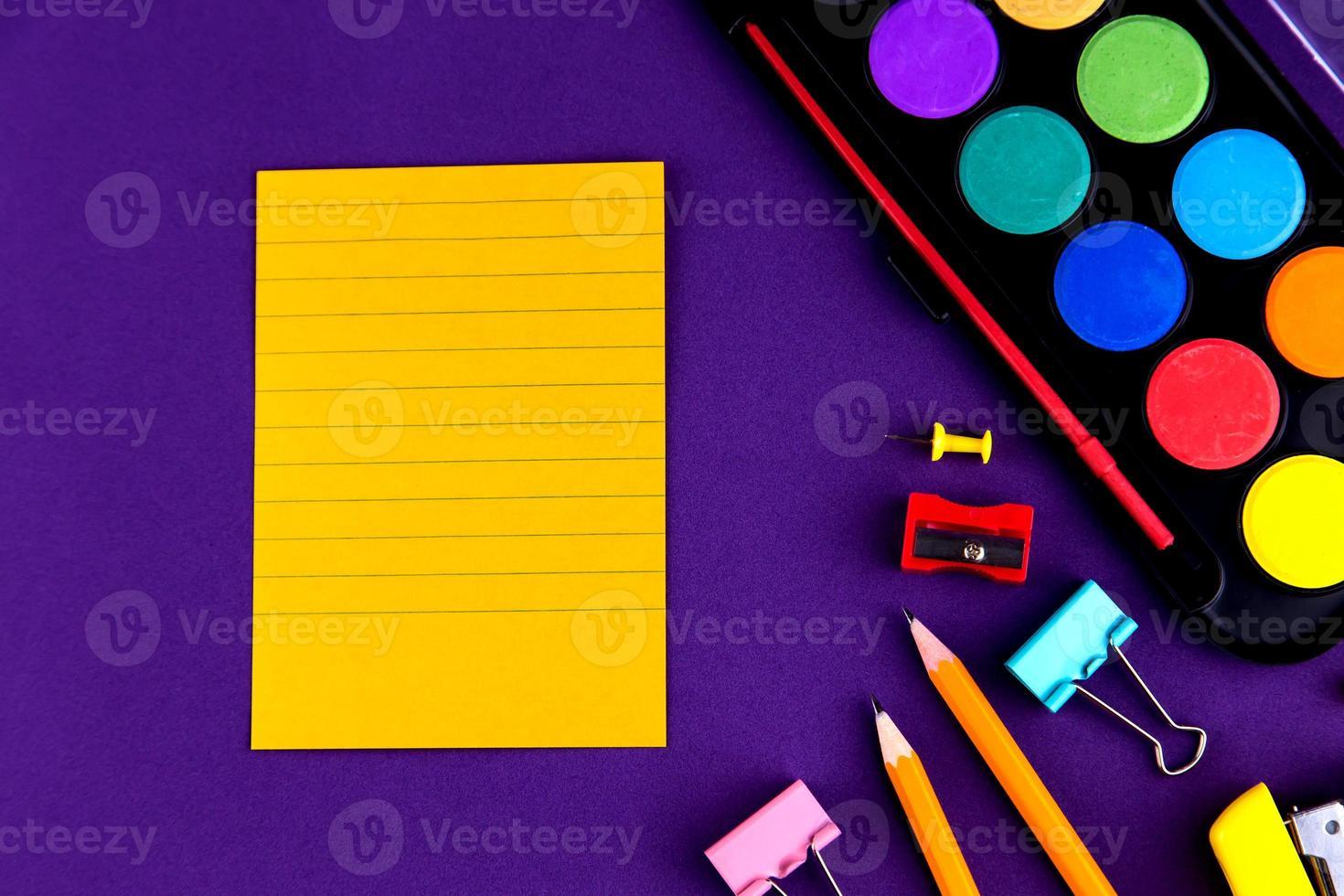 material de oficina escolar papelería sobre un fondo morado foto