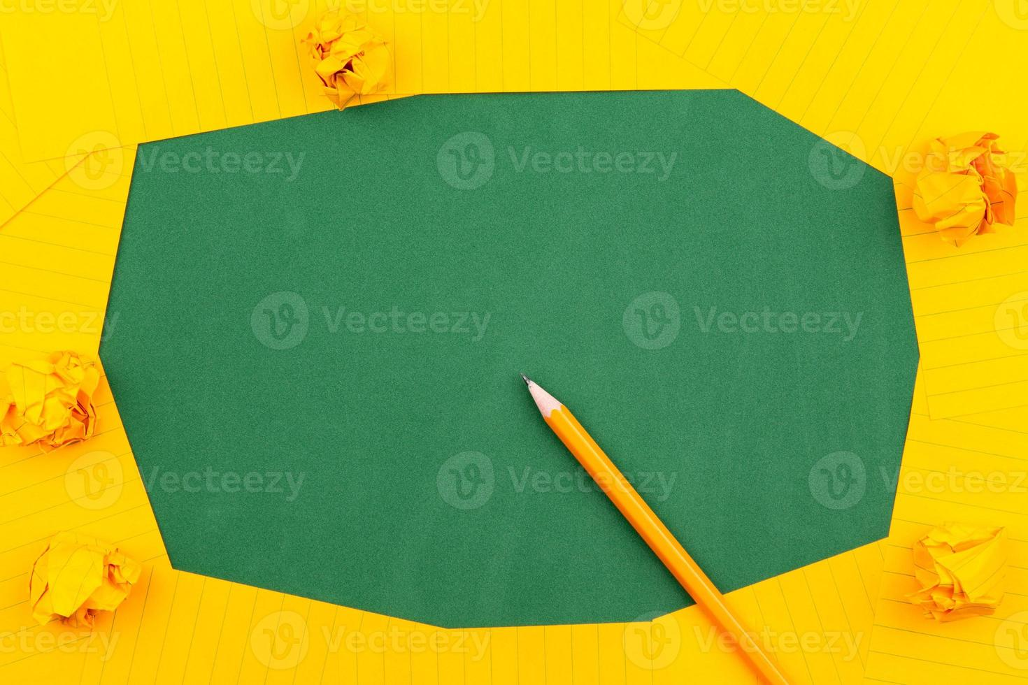 An orange sheet of paper lies on a green school board photo