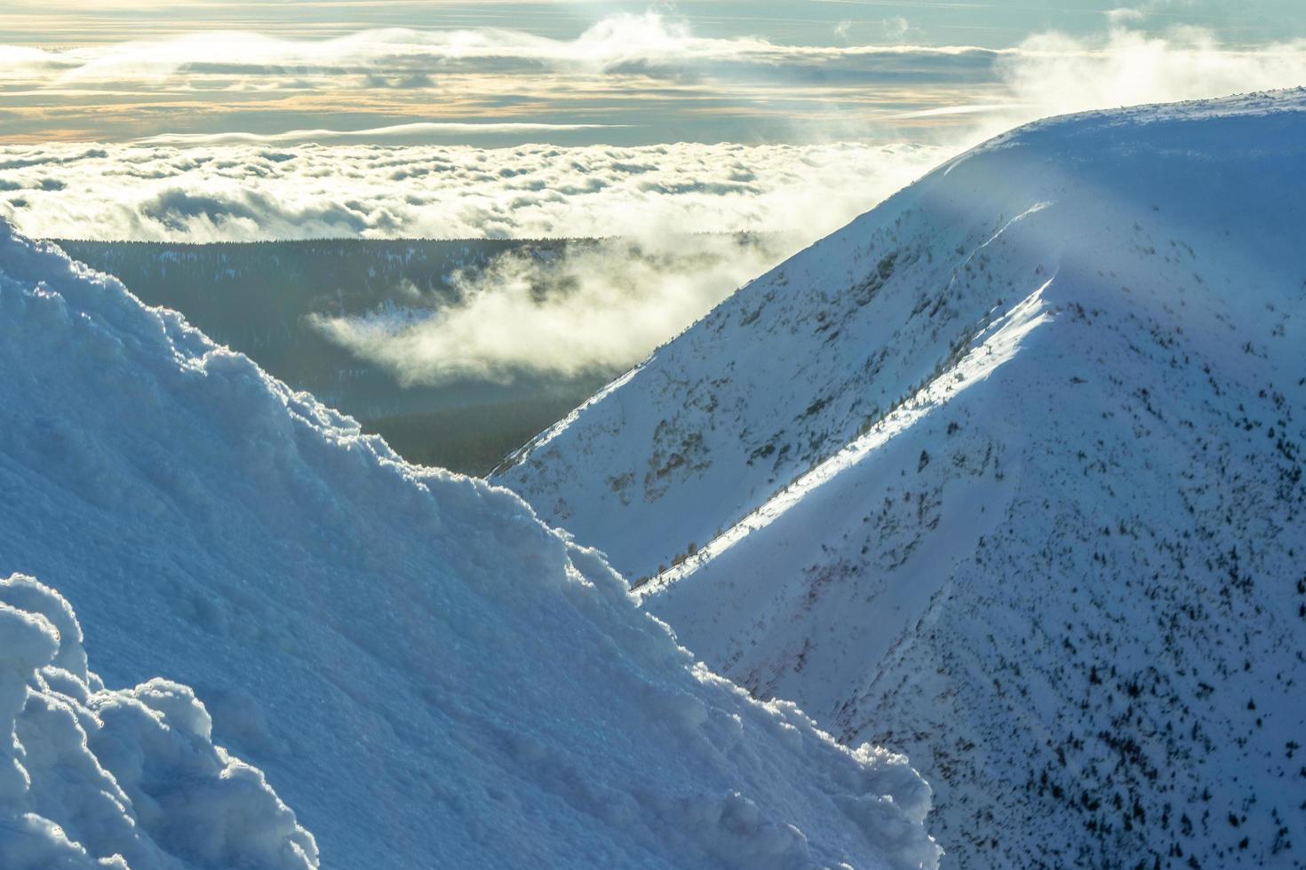 Snow mountains on sunny sky photo