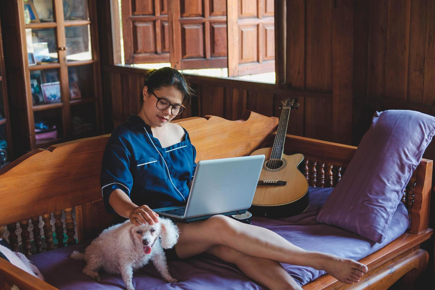 young woman working on laptop at home cute small dog besides work from home photo