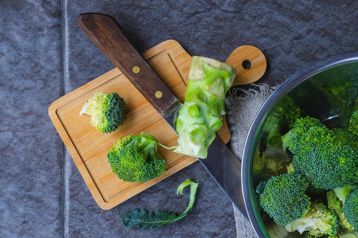 Brócoli crudo cortado en una tabla de cortar de madera foto