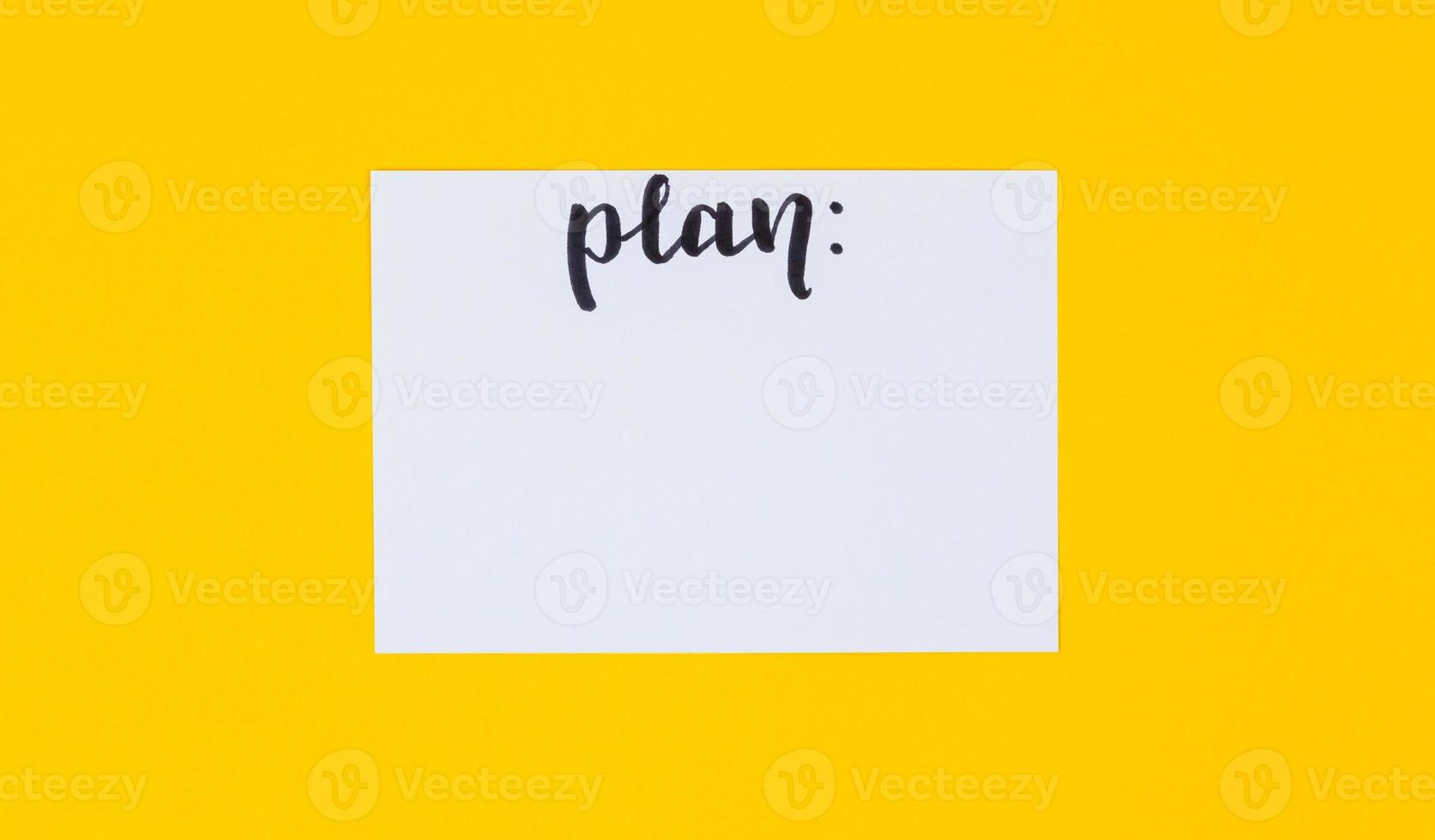papel blanco en blanco e inscripción caligráfica negra del plan de palabra sobre fondo amarillo foto