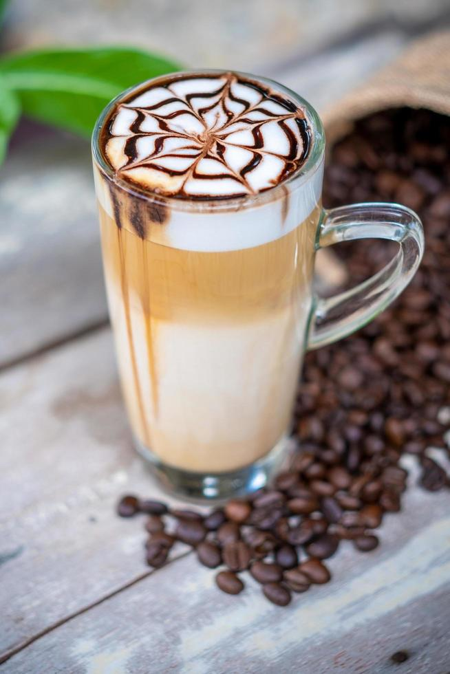 café con leche macchiato caliente con arte de jarabe de chocolate foto