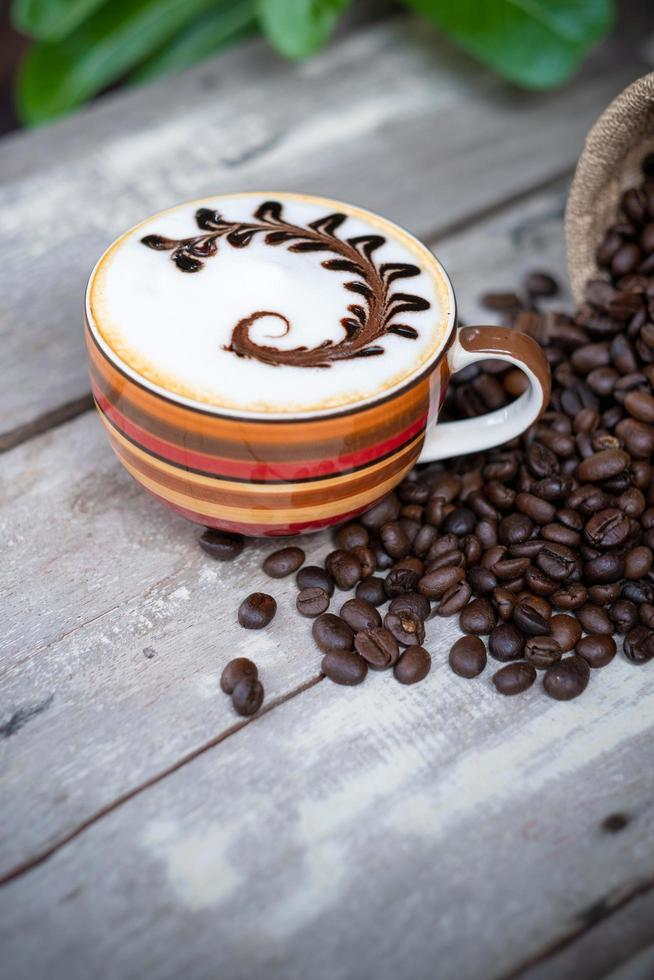 Hot cappuccino coffee on old wooden table with roasted coffee beans photo
