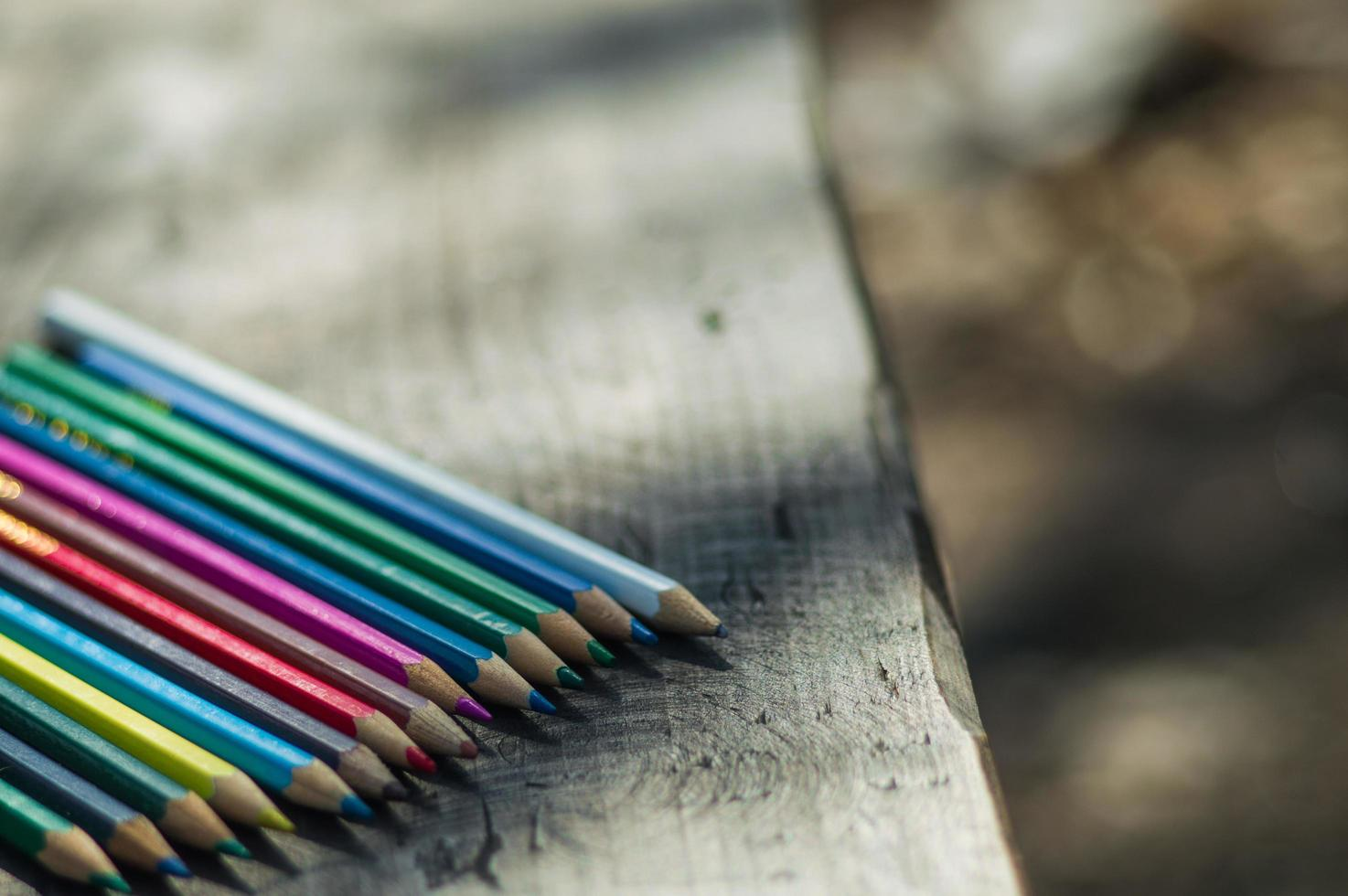 Pencils of different colors on a the bench photo