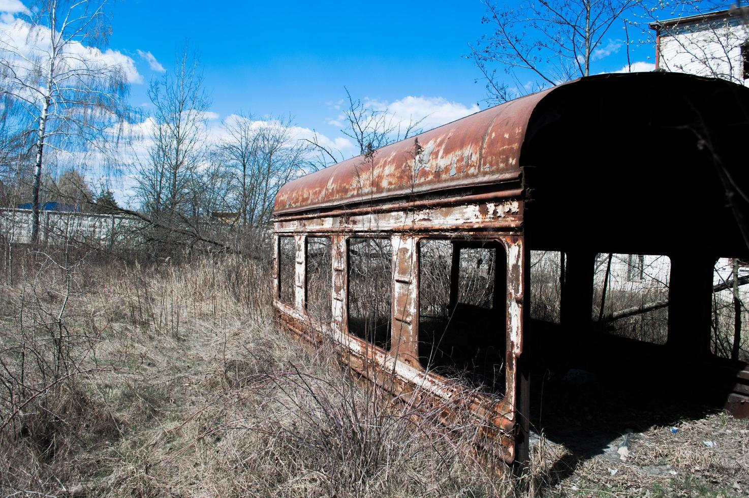 Old rusty carriage in dry grass photo