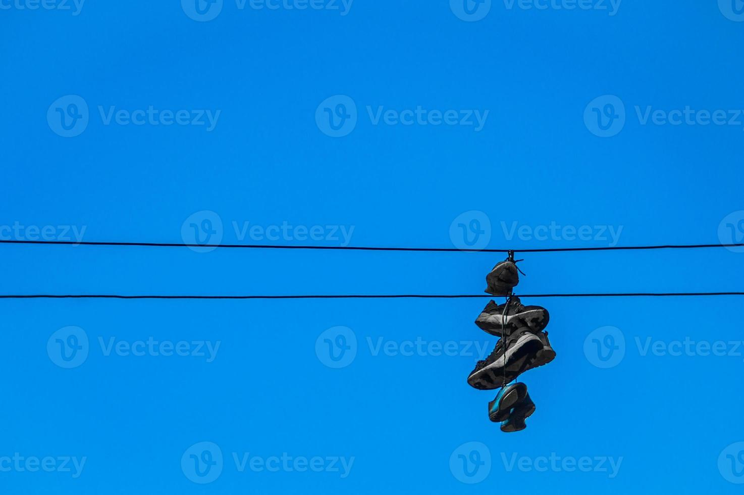 Sneakers hanging on wires against a blue sky photo