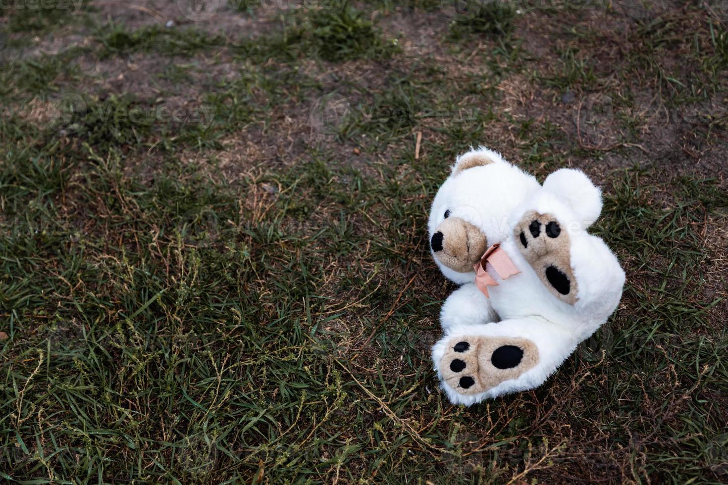 Lost abandoned soft plush toy teddy bear sitting on ground photo