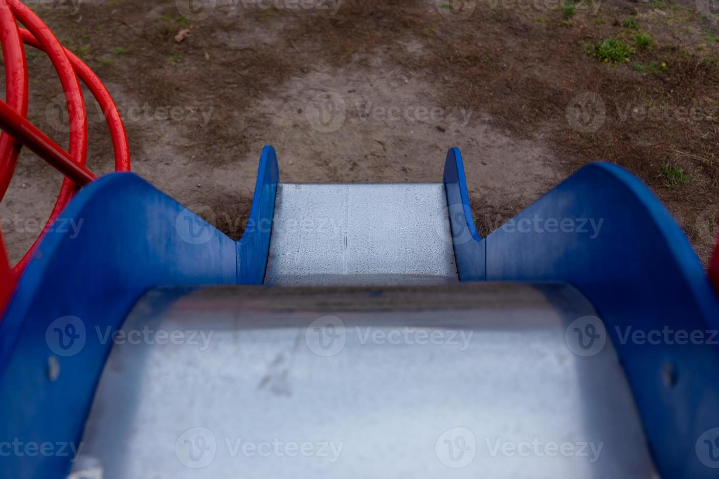 Children's slide with blue sides and a shiny metal surface photo