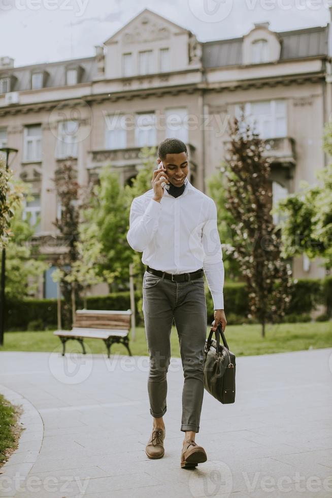 Young African American businessman using a mobile phone on a street photo