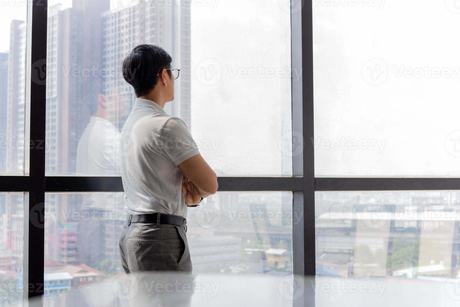 Businessman standing in office with hands crossed looking through window  building photo