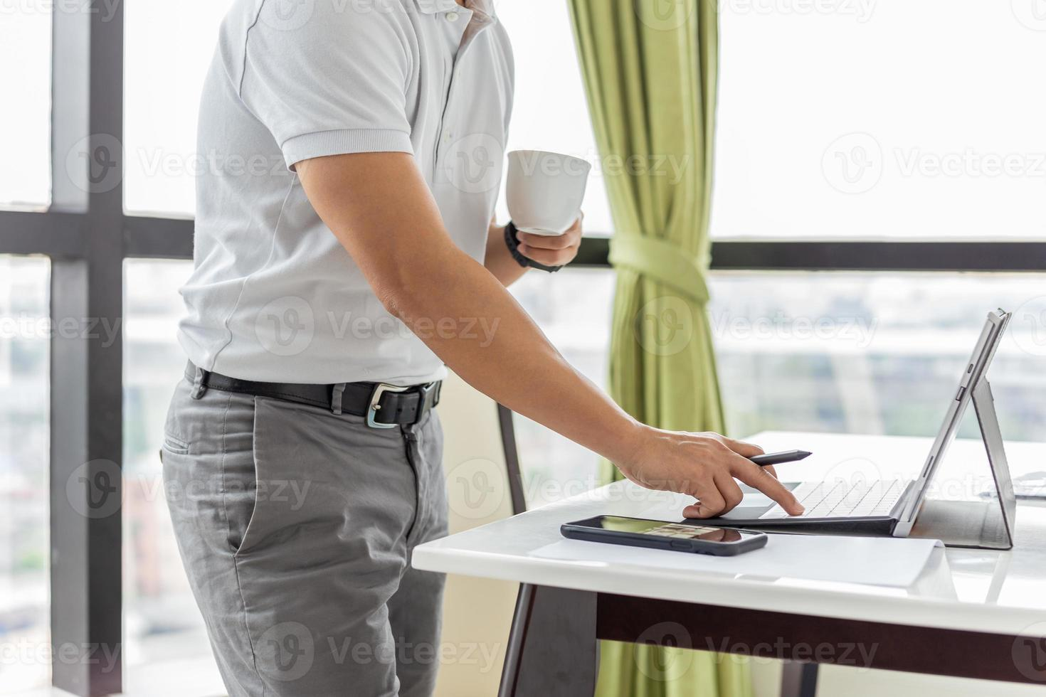 Businessman checking email on laptop and holding cup coffee photo