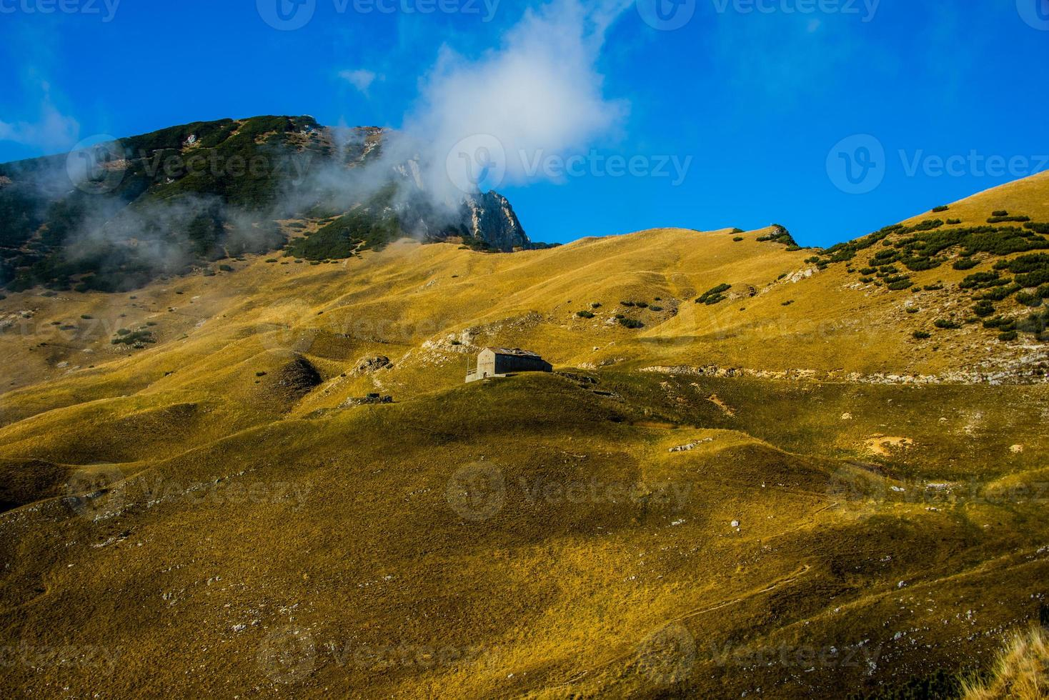 choza entre los campos amarillos de otoño en los alpes foto