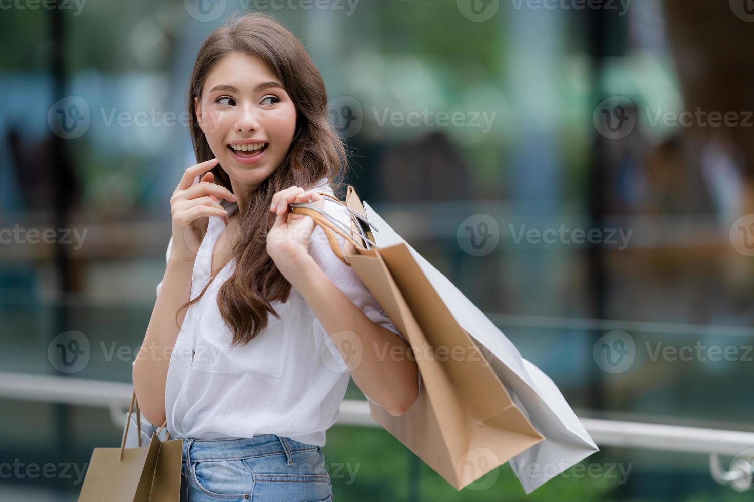 Retrato al aire libre de mujer feliz sosteniendo bolsas de la compra y cara sonriente foto