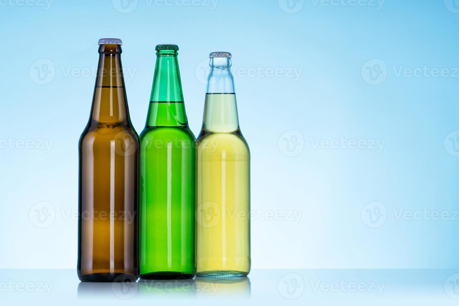Group of Three bottles of beer on blue background photo