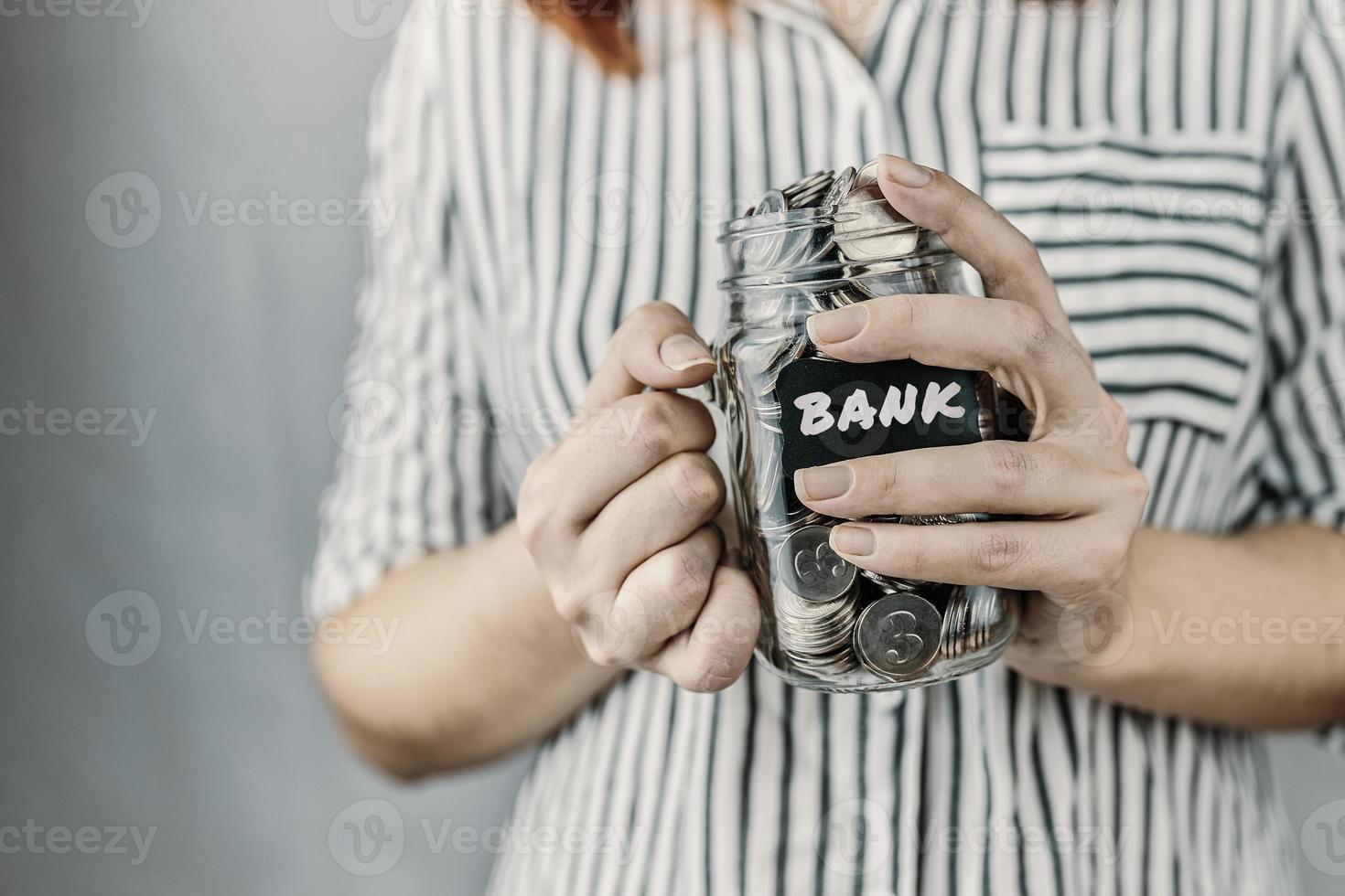 botella de vidrio con monedas en manos de mujeres foto
