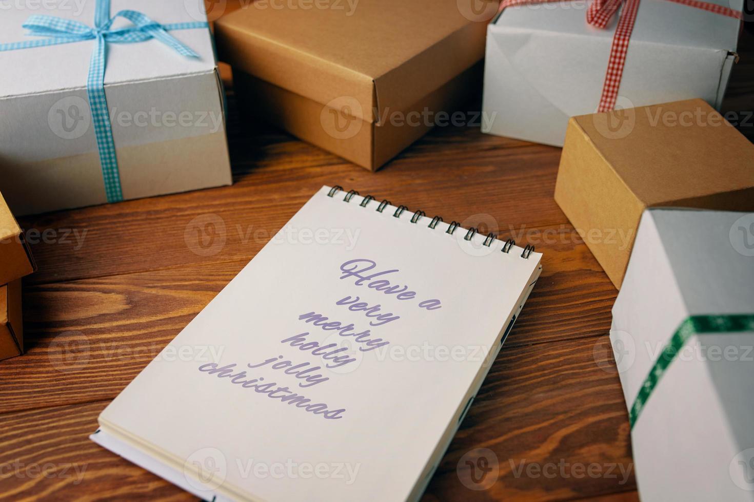 mesa de madera con cajas de regalo y bloc de notas foto