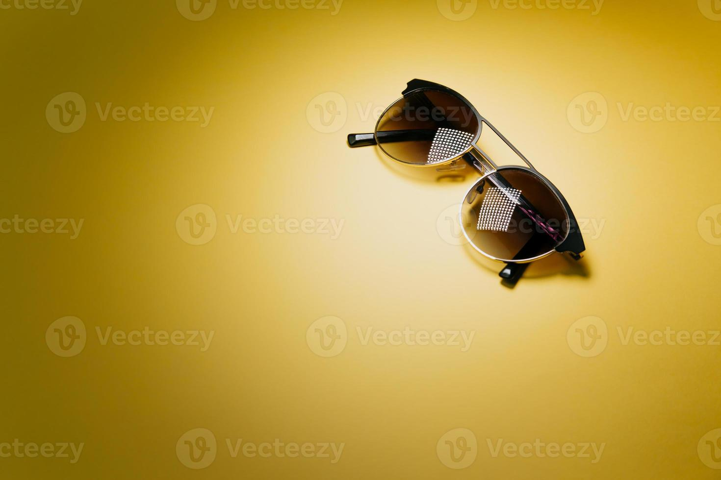 Pair of sunglasses over a pastel yellow background with copy space photo