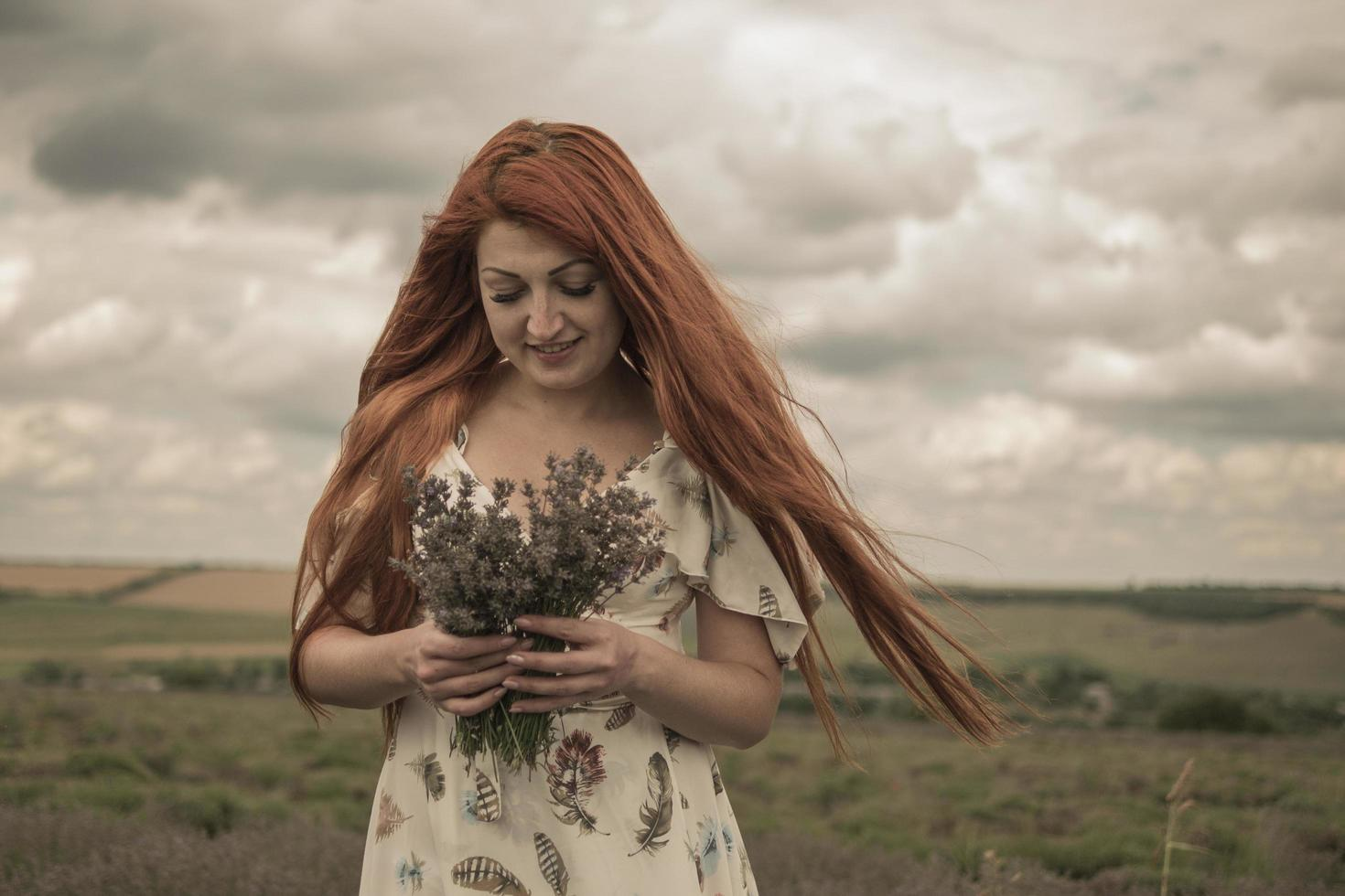 portrait of a red haired young girl in a white dress in a field with a bouquet of lavender photo