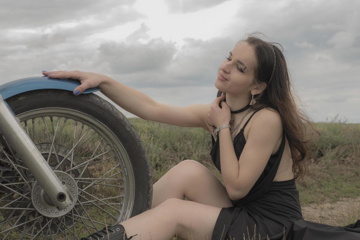ciclista morena en una motocicleta en el campo de lavanda contra el cielo con nubes lenta foto