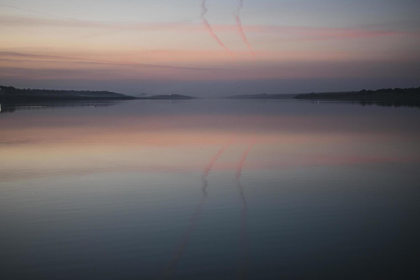 neblina sobre el agua al atardecer puesta de sol sobre el lago foto