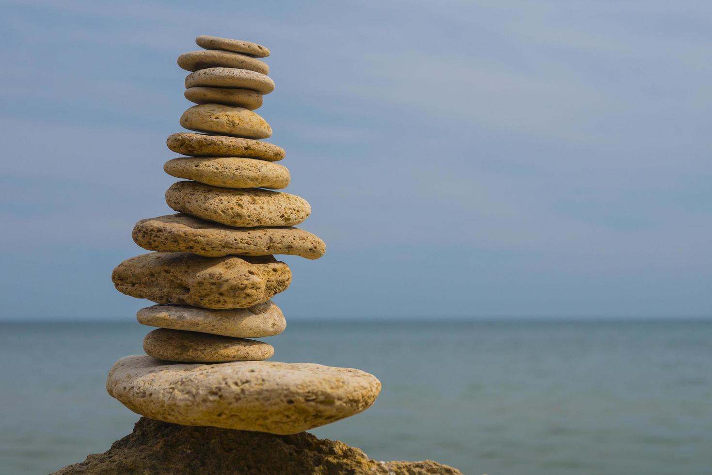 Equilibrio de pirámide de piedras sobre una gran piedra en la orilla del mar foto