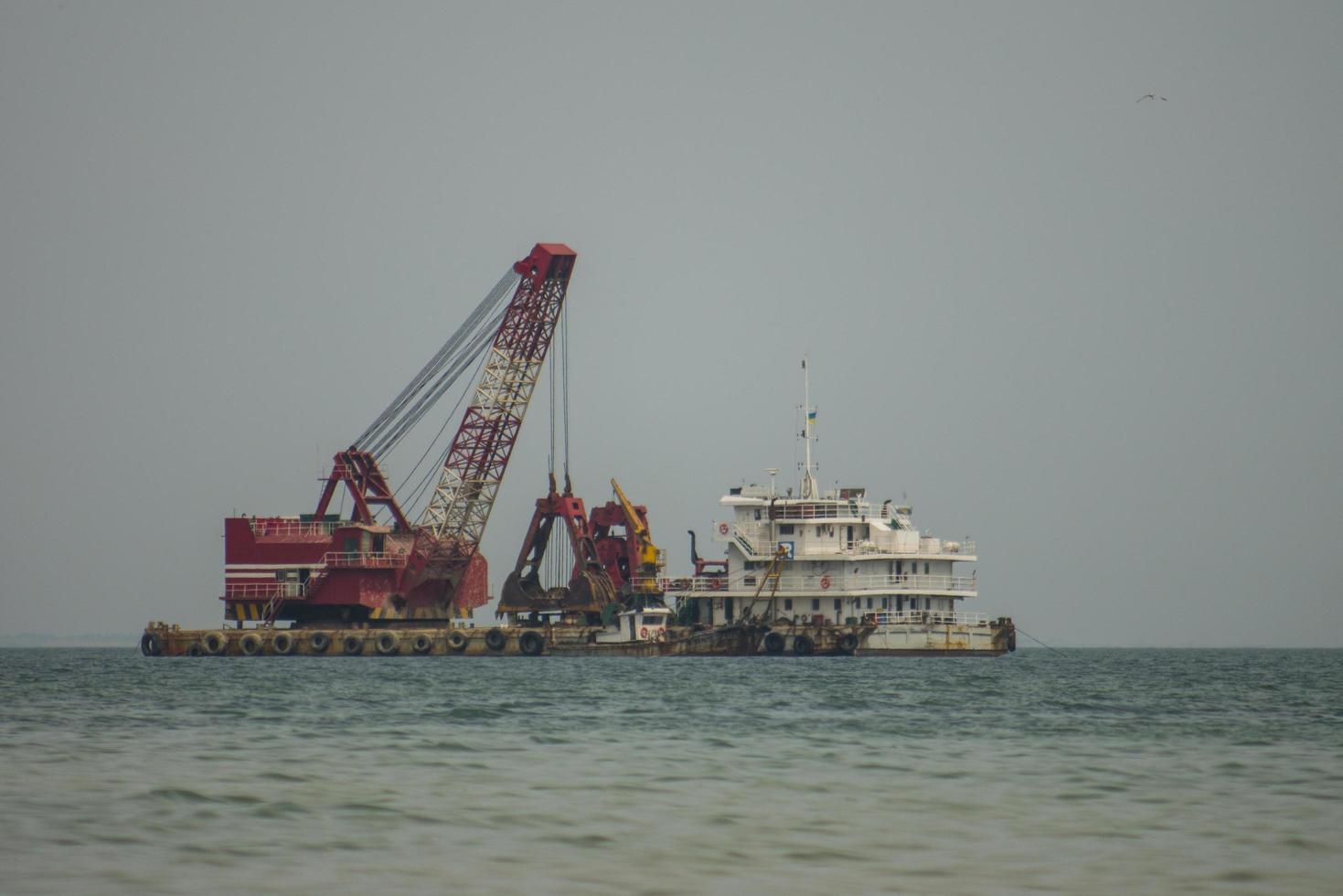 La grúa flotante y el buque de carga están trabajando en el mar. foto